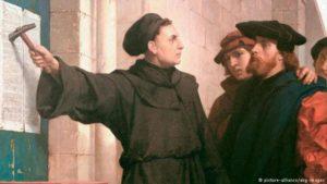"""Мартин Лутер заковава своите емблематични """"95 тезиса"""" на вратата на местната дворцова църква във Витемберг."""